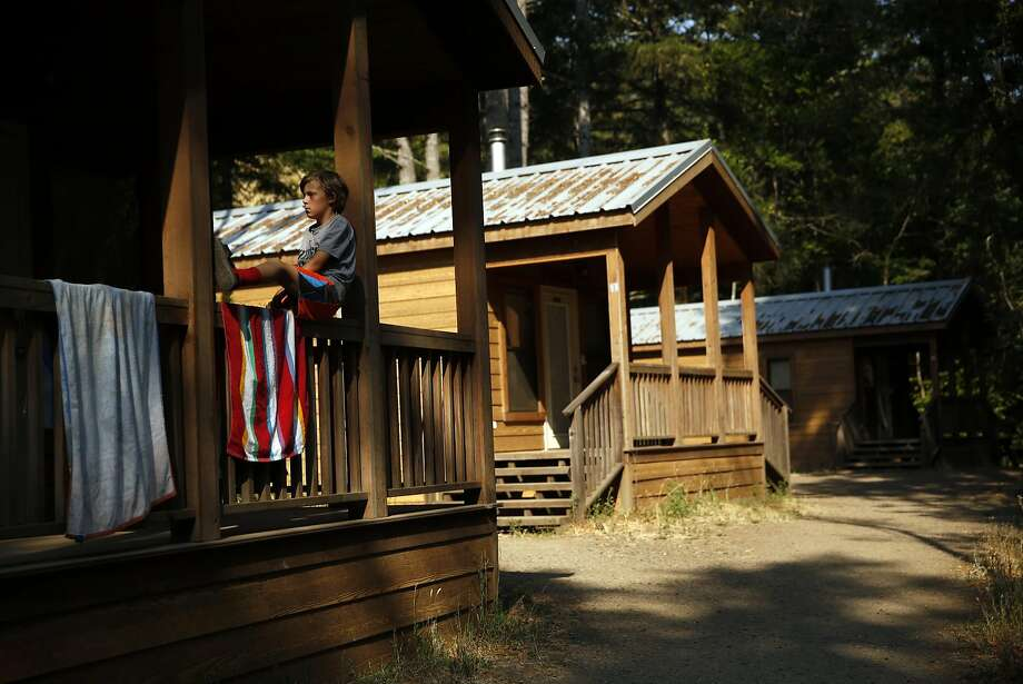 Isaac Petersen relaxes on the porch of his family's well-appointed rental cabin in Samuel P. Taylor State Park in Marin County. Photo: Scott Strazzante, The Chronicle
