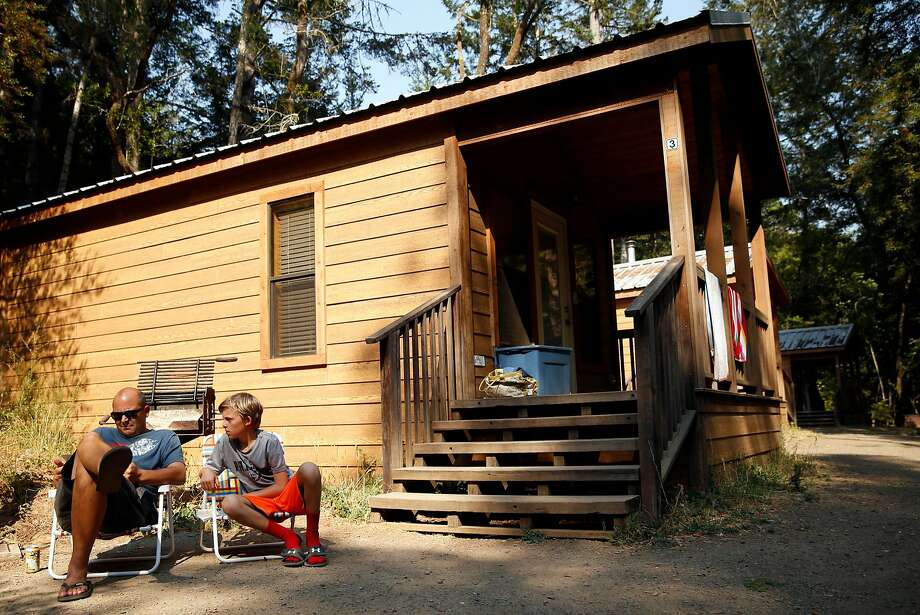 Joe Petersen of Berkeley and son Isaac relax outside their rented cabin in Samuel P. Taylor State Park in Lagunitas.. Photo: Scott Strazzante, The Chronicle