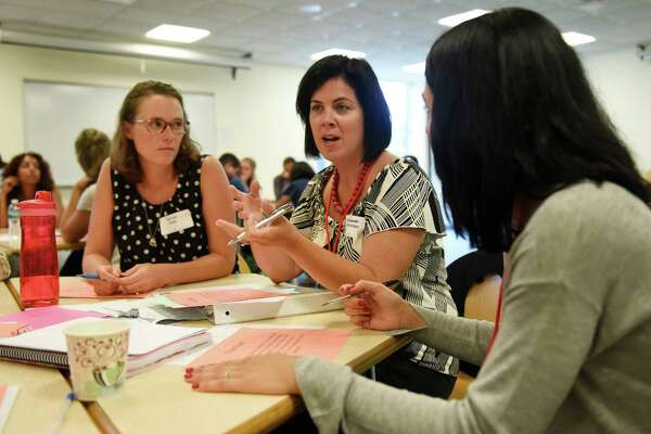 New Julian Curtiss School fifth-grade teacher Keturah Engle, left, and special education teacher Liz DellaVolpe discuss teaching strategies on day two of new teachers' orientation in the media center at Greenwich High School in Greenwich, Conn. Thursday, Aug. 25, 2016. Superintendent Sal Corda addressed the group as they discussed professional development and made goals for the upcoming school year.