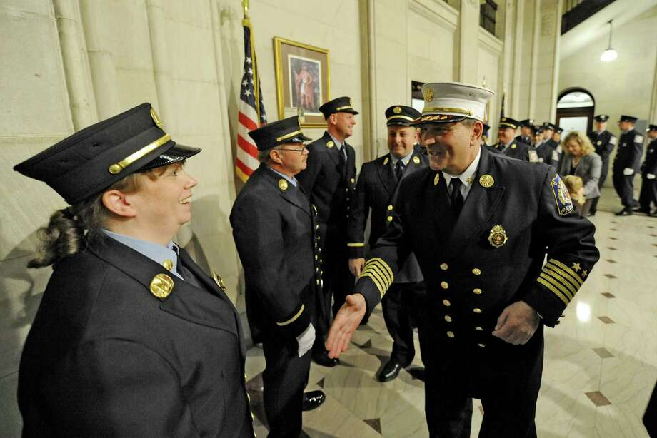 In this November 2011 file photo, newly promoted Captain Maria Walker, left is greeted by Albany Fire Department Chief Bob Forezzi after the promotion ceremony in City Hall in Albany, N.Y. Walker was the first woman to be promoted to Captain in the history of the Albany Fire Department.  (Skip Dickstein/Times Union) Photo: Skip Dickstein / 2011