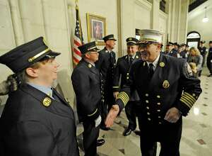 In this November 2011 file photo, newly promoted Captain Maria Walker, left is greeted by Albany Fire Department Chief Bob Forezzi after the promotion ceremony in City Hall in Albany, N.Y. Walker was the first woman to be promoted to Captain in the history of the Albany Fire Department.  (Skip Dickstein/Times Union)