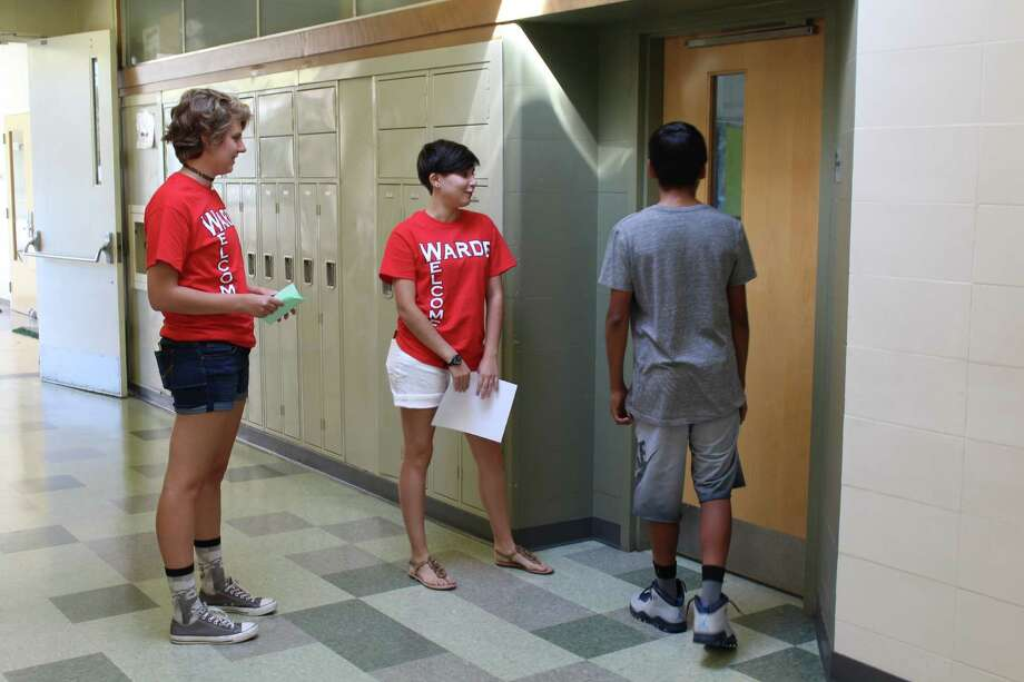 Rising seniors Anna Peterson, left, and Gabriella Petrone give incoming freshman Jorge Rojas a tour through the halls of Fairfield Warde High School in Fairfield, Conn. on Aug. 24, 2016. Photo: Laura Weiss / Hearst Connecticut Media / Fairfield Citizen