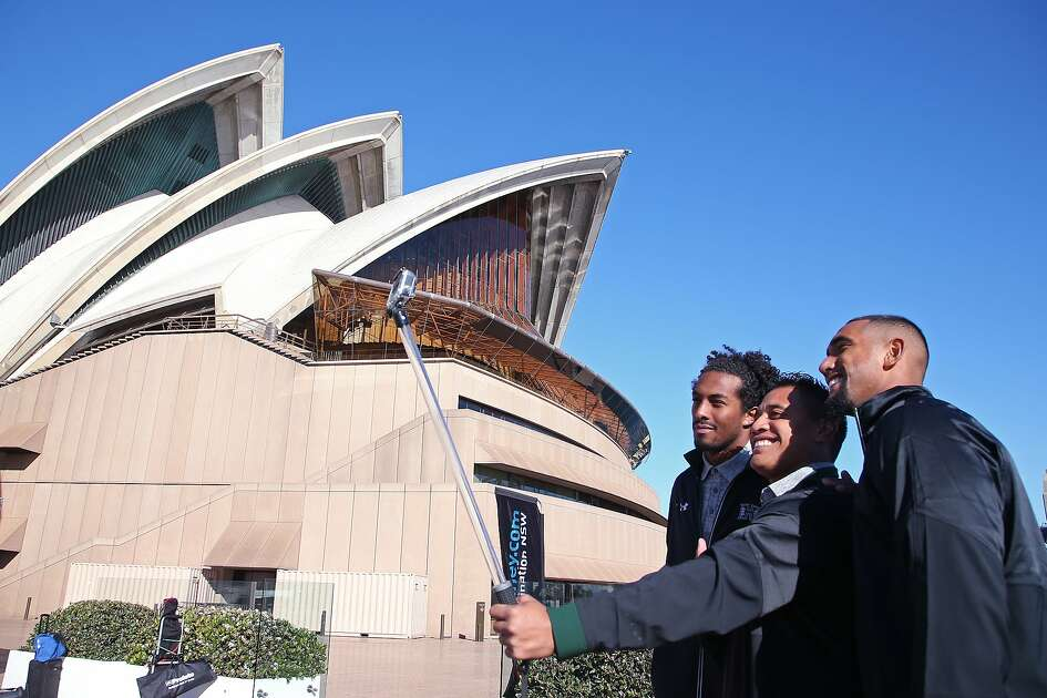 Hawaii Rainbow Warriors' players Marcus Kemp, left, Steven Lakalaka and Makan Kema-Kaleiwahia, right, take advantage of the sites around Sydney to take photos at the Opera House, Tuesday, Aug. 23, 2016, ahead of their opening college football game of the season against the California Golden Bears on Saturday. The game, with Cal designated as the home team, will be the first college football game played in Sydney and the first significant American football game played in Australia since 1999. (AP Photo/Rick Rycroft)