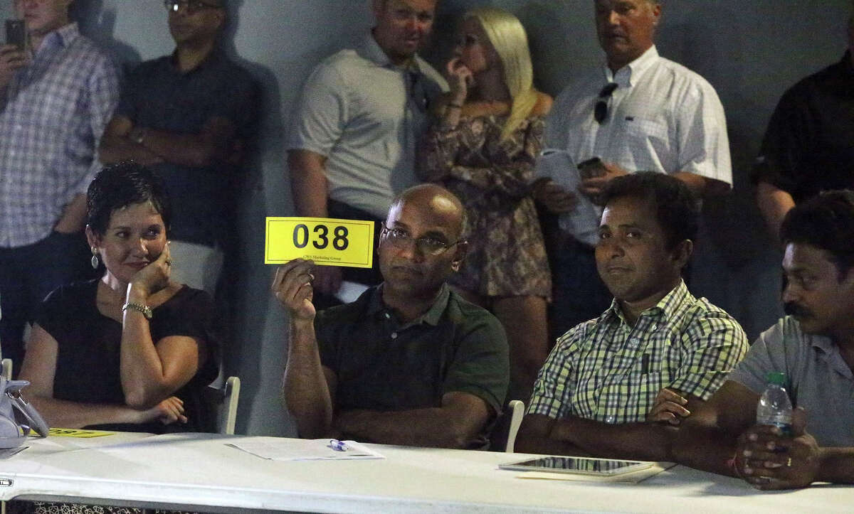 A bidder shows his number Thursday August 15, 2015 at the site of a retail strip center at Redland Road and U.S. Highway 281 North that was auctioned off by the Internal Revenue Service. Known as the North Pointe Retail Center, it is one of eight properties forfeited to the federal governmentas part of a money-laundering investigation. It sold for $6,750,000. (Six million, seven hundred and fifty thousand dollars). The man holding the #038 card won the auction but would not release his name.