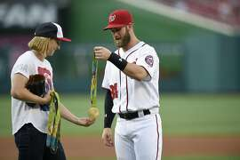 Washington Nationals' Bryce Harper, right, gives back Olympic gold-medal swimmer Katie Ledecky, left, her medals after she threw out the ceremonial first pitch before a baseball game between the Baltimore Orioles and the Washington Nationals, Wednesday, Aug. 24, 2016, in Washington. (AP Photo/Nick Wass)