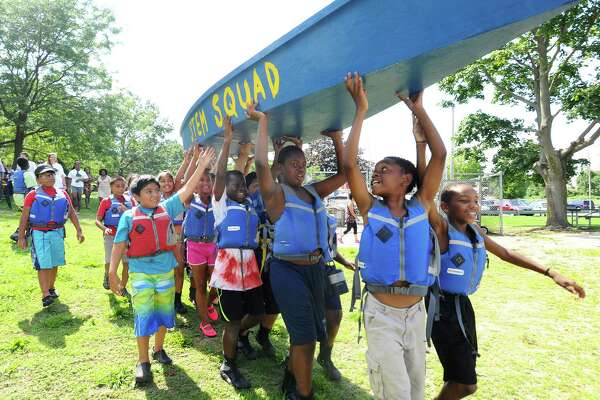 Brian Augustine, 11, (second from right), a fifth-grader at Westover Elementary School, leads the SoundWaters campers as they carry their homemade boat to the water for the first time Thursday at Boccuzzi Park in Stamford.