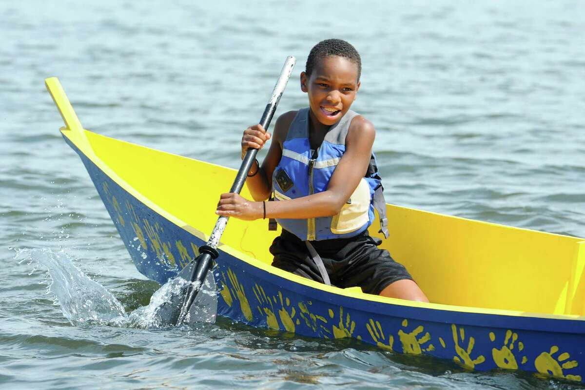 """Jaylen Brown, 10, who will be a fifth-grader at Northeast Elementary School, steers the """"STEM Squad"""" boat on Long Island Sound."""