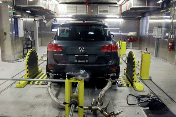 A Volkswagen Touareg diesel is tested in the Environmental Protection Agency's cold temperature test facility in Ann Arbor, Mich. Volkswagen has reached a tentative deal with its U.S. dealers to compensate them for losses they said they suffered as a result of the company's emissions cheating scandal.