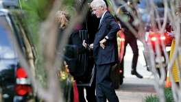 Former president Bill Clinton returns to his car to get something he had forgotten upon entering as he visits the home of Henry Munoz III in San Antonio for a private fundraiser benefiting his wife Hillary Clinton on August 25, 2016