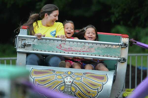 Nicole Kazantzidis takes her twin 6-year-old nieces Leianna and Katenna Cross for a spin on the scrambler during opening night of the St. George Greek Orthodox Church Greek Festival on Thursday night in Norwalk.