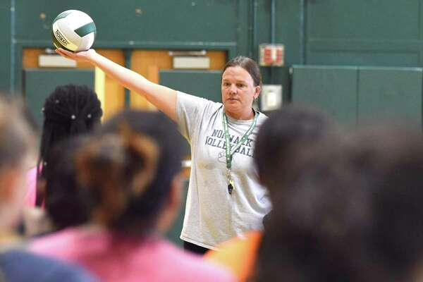 Norwalk High assistant volleyball coach Karey Fitzgerald holds up a ball for some of her younger players to hit while running a drill during Thursday's opening day of fall sports practices at Scarso Gymnasium in Norwalk.
