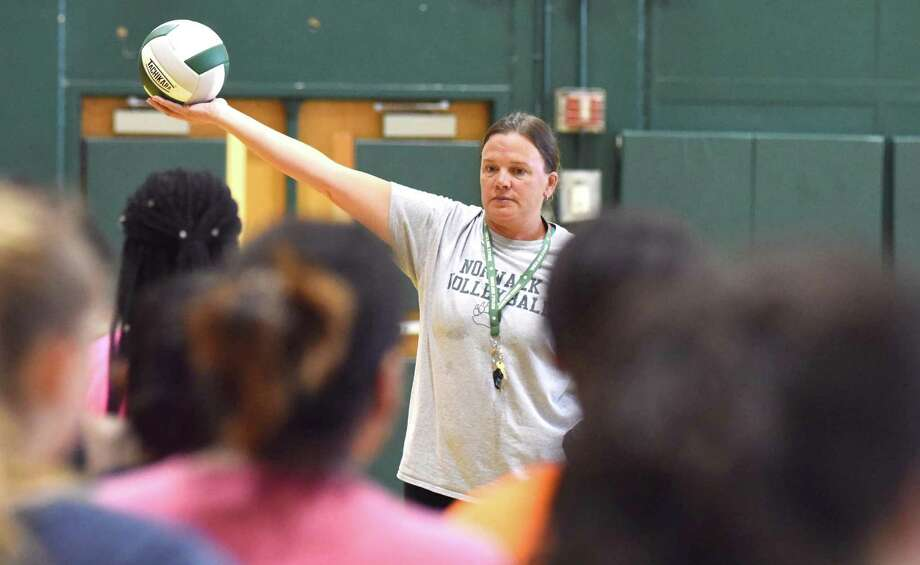 Norwalk High assistant volleyball coach Karey Fitzgerald holds up a ball for some of her younger players to hit while running a drill during Thursday's opening day of fall sports practices at Scarso Gymnasium in Norwalk. Photo: John Nash / Hearst Connecticut Media / Norwalk Hour