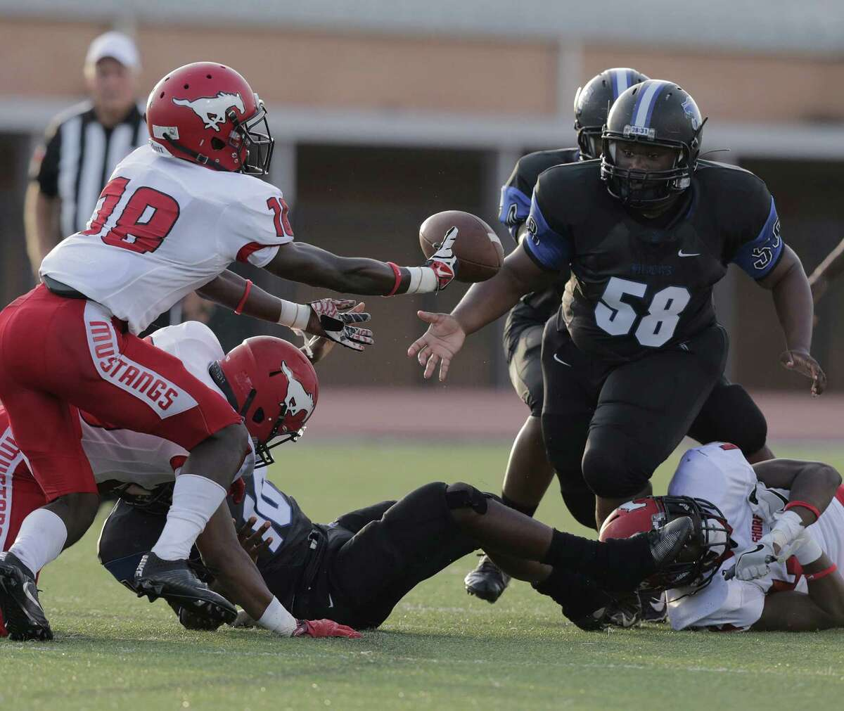 Dekaney's Quincy Gentry (58) watches a fumbled football as North Shore's Jaylen Thomas (18) goes for it on Thursday, Aug. 25, 2016, in Spring. Dekaney recovered the ball.