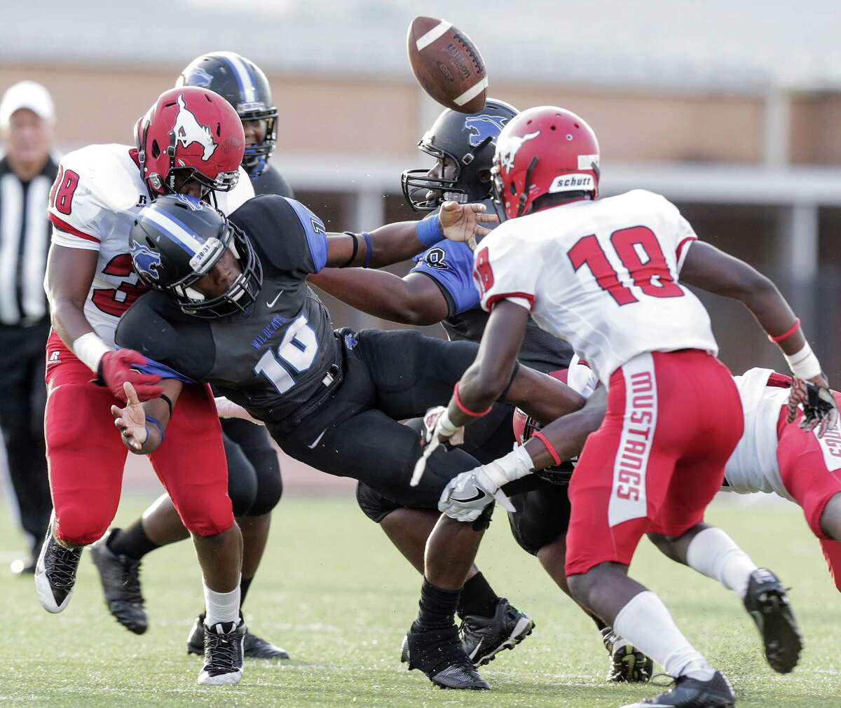 Dekaney's Jerry Wells (10) fumbles the ball after being hit against North Shore on Thursday, Aug. 25, 2016, in Spring. Dekaney recovered the football.