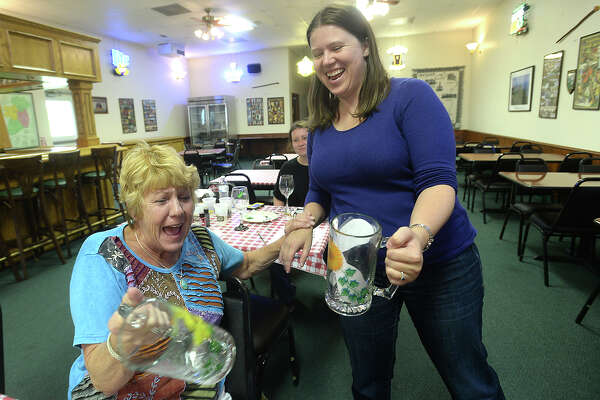 Becca Amy (left) and Amanda Blankenship crack up and pretend a toast as they realize both have painted their beer mugs with similar flower themes during the monthly Painting in the Pub event held Thursday night at the Clifton Steamboat Museum's O'Hearns Pub. Women gathered with snacks and beverages and worked on painting wine glasses and beer mugs.  Photo taken Thursday, August 25, 2016 Kim Brent/The Enterprise