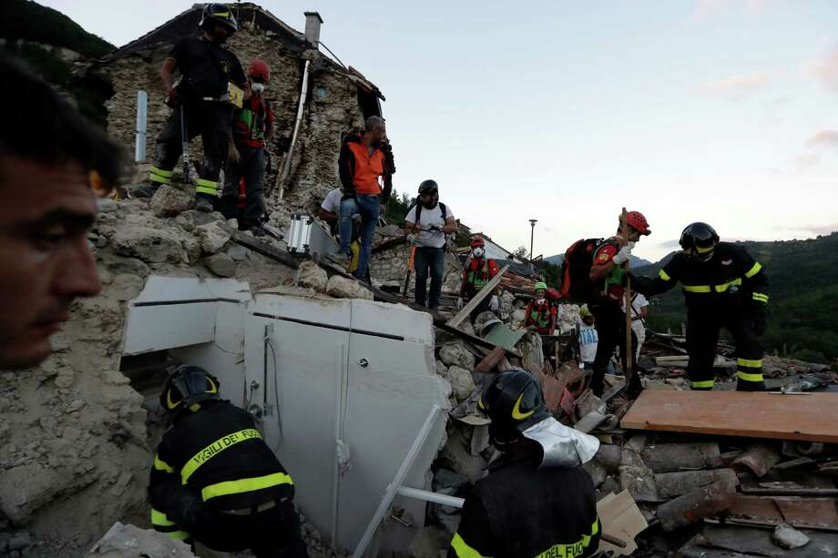 Rescuers search through debris following an earthquake in Pescara Del Tronto, Italy, Wednesday, Aug. 24, 2016. The magnitude 6 quake struck at 3:36 a.m. (0136 GMT) and was felt across a broad swath of central Italy, including Rome where residents of the capital felt a long swaying followed by aftershocks.  (AP Photo/Andrew Medichini) ORG XMIT: AJM150 Photo: Andrew Medichini / Copyright 2016 The Associated Press. All rights reserved. This m