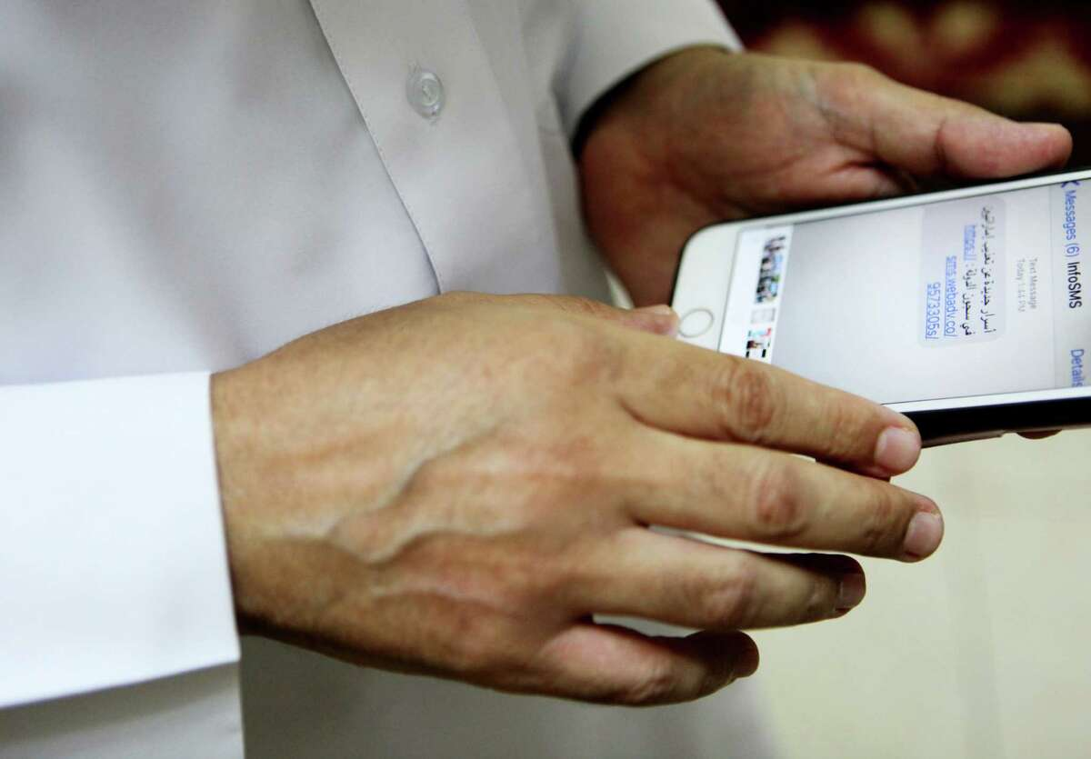 Human rights activist Ahmed Mansoor shows Associated Press journalists a screenshot of a spoof text message he received in Ajman, United Arab Emirates, on Thursday, Aug. 25, 2016. Mansoor was recently targeted by spyware that can hack into Apple's iPhone handset. The company said Thursday it was updated its security. The text message reads: