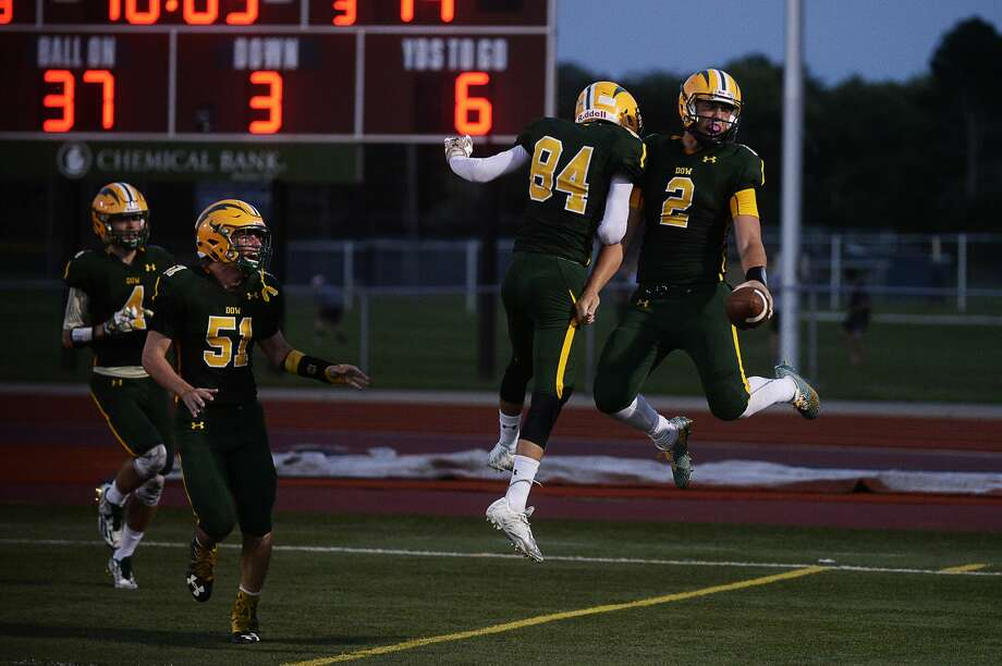 ERIN KIRKLAND | ekirkland@mdn.net  Dow's Bruce Mann, right, celebrates with teammate Austin Stredney, left, Mann scored a touchdown on Thursday at Midland Community Stadium. Photo: Erin Kirkland/Midland Daily News