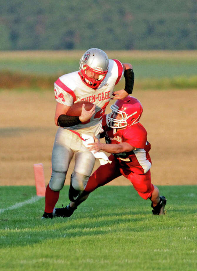 Owen-Gage running back David Binder (34) tries to shake a tackle in the first half of the Bulldogs' 44-0 victory over Caseville, Thursday night, in Caseville. Binder ended with 103 yards on seven carries and three touchdowns.