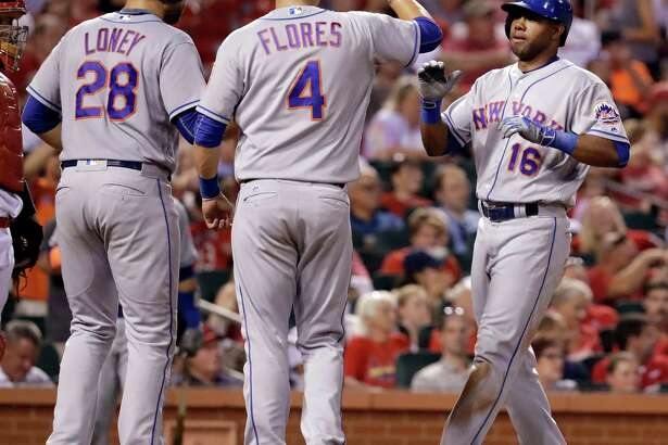 New York Mets' Alejandro De Aza, right, is congratulated by teammates James Loney (28) and Wilmer Flores (4) after hitting a three-run home run during the fifth inning of a baseball game against the St. Louis Cardinals Thursday, Aug. 25, 2016, in St. Louis. (AP Photo/Jeff Roberson) ORG XMIT: MOJR113