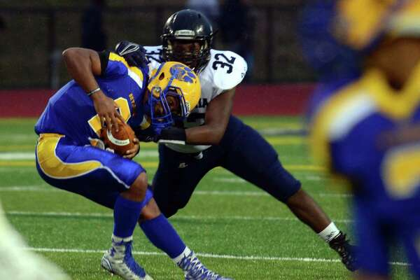 Ansonia's Malcolm Martin makes certain Seymour's Jaylen Kelly doesn't get away in a game last season.