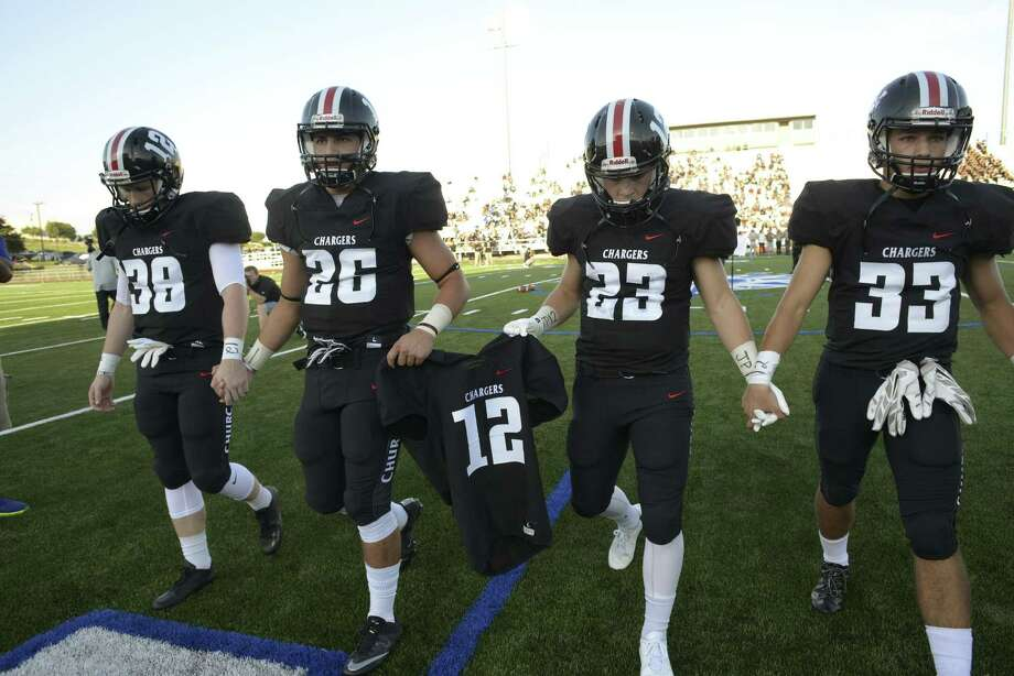 Churchill High School football team captains Tyler Ellis, left, Grant Gomez, Thomas Sharrick and Nicholas Sandoval carry the jersey of teammate Josh Pollard, who died recently from an unknown heart ailment, before the team's opening game against Clark High School in the annual Gucci Bowl at Commander Stadium on Aug. 25, 2016. Photo: Billy Calzada /San Antonio Express-News / San Antonio Express-News