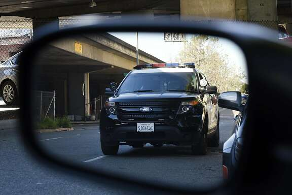 A police cruiser is seen in a rearview mirror as it drives along 6th St. in Oakland, CA Thursday, March 17, 2016.