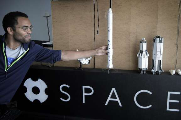 Chief Technology Officer Blaze Sanders picks up a scale model of a SpaceX spacecraft at the SpaceVR offices in San Francisco, Calif., on Thursday, August 25, 2016, with Lead Space Engineer, Varun Vruddhula, rear.   San Francisco startup SpaceVR landed a deal to get its shoe-box sized satellite, the Overview 1, launched into space, delivered to the International Space Station and then deployed in low-earth orbit, in 2017, to deploy a network of satellites loaded with 360-degree video cameras to let people on earth get a virtual reality view of what it?s like to be orbiting the earth