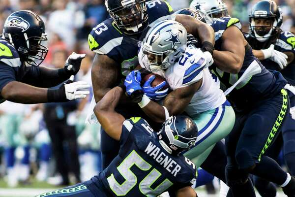 Dallas Cowboys running back Ezekiel Elliott is tackled by the Seahawks defensive line during the first quarter of the Seahawks' 27-17 win at Century Link Field in Seattle on Aug. 25, 2016.