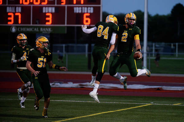ERIN KIRKLAND | ekirkland@mdn.net  Dow High quaterback Bruce Mann (2), celebrates with teammate Austin Stredney, left, after Mann scored a touchdown in Thursday's game at Midland Stadium.