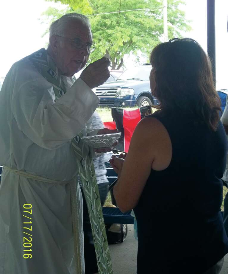 Father Joseph Schabel hands out communion at the picnic. (Submitted Photo)