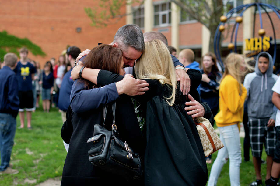 Terry Hanley hugs Steven Szymanski's parents, John and Dawn, and sister, Ashlie, in this 2015 file photo after a ceremony to honor the fallen Marine at Midland High School. / Midland Daily News