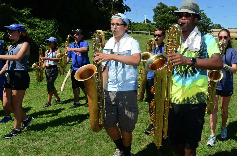 Members of the Norwalk High School Marching Bears, including Baritone Sax player Katrall Clay, right, practice during the high school's annual summer band camp at Andrews Field. Color guard member Zoe Harris, below. Photo: Erik Trautmann / Hearst Connecticut Media / Norwalk Hour