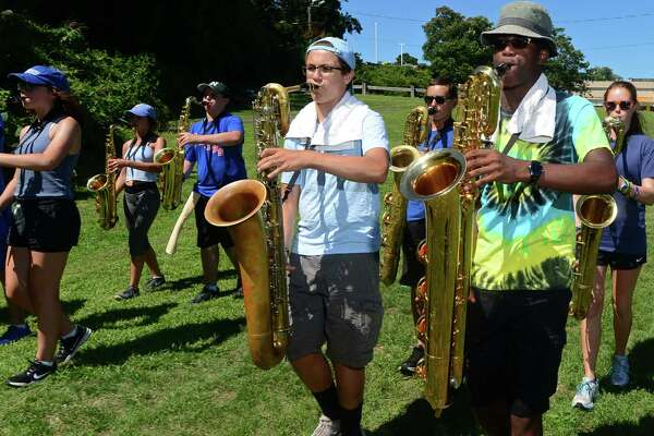 Members of the Norwalk High School Marching Bears, including Baritone Sax player Katrall Clay, right, practice during the high school's annual summer band camp at Andrews Field. Color guard member Zoe Harris, below.