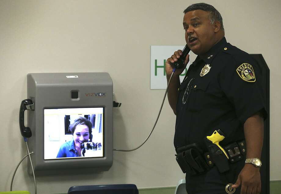 Bexar County Chief Jail Administrator Raul Banasco demonstrates a new video visitation system in August 2016. County employee Teresa Guerrero-Livengood is shown on the other end of the call. Photo: John Davenport, San Antonio Express-News