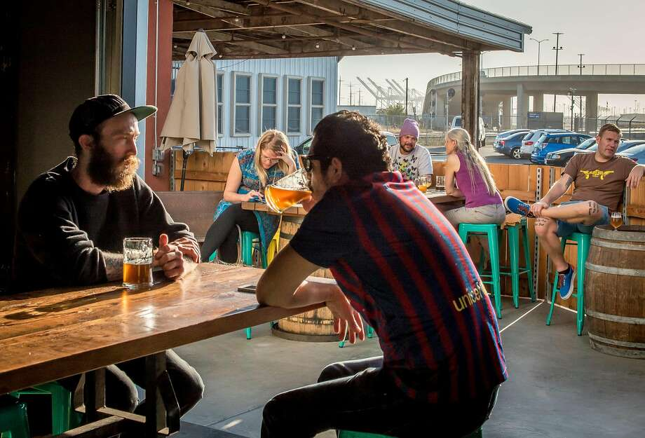People have beers at the Beer Shed next to the Dock at Linden Street in Oakland. Photo: John Storey, Special To The Chronicle