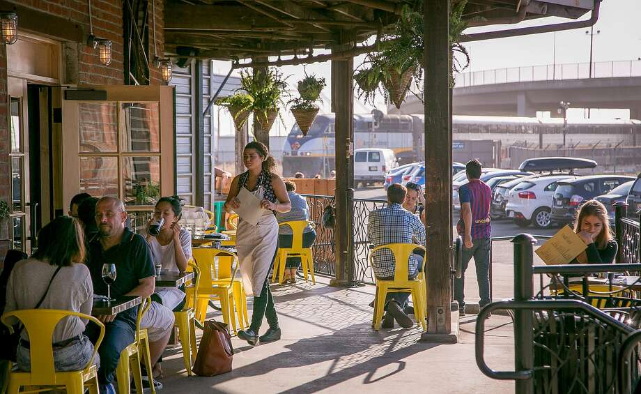 People have dinner outside at the Dock at Linden Street in Oakland. Photo: John Storey, Special To The Chronicle
