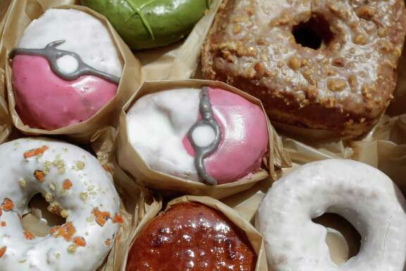 """Pecha Berry Pokéseed doughnuts are displayed with other doughnuts in a box from Doughnut Plant, in New York. From doughnut shops to zoos, businesses and organizations are finding creative ways to capitalize on """"Pokémon Go."""""""