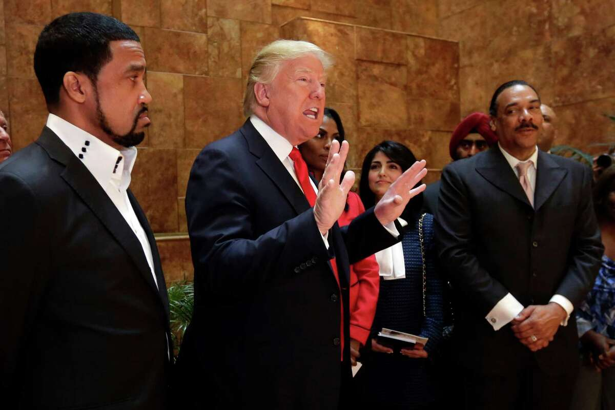 FILE - In this April 18, 2016 file photo, Pastor Darrell Scott listens at left as Republican presidential candidate Donald Trump speaks in Trump Tower building in New York. Competing appearances earlier this month by Trump and Hillary Clinton highlight an oft-overlooked political reality: The ?