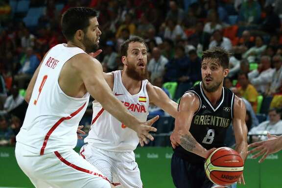 Nicolas Laprovittola of Argentina works against Sergio Rodriguez (center) and Felipe Reyes (left) of Spain during a men's preliminary round game at Carioca Arena 1 on Aug. 15, 2016 in Rio de Janeiro.