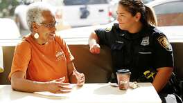 SAFFE Officer Tina Castillo listens toPat Kennedy at a Coffee and Cops event. Programs like SAFFE provide positive communication between police and citizens and tangible ways for residents to see the city investing in their safety.