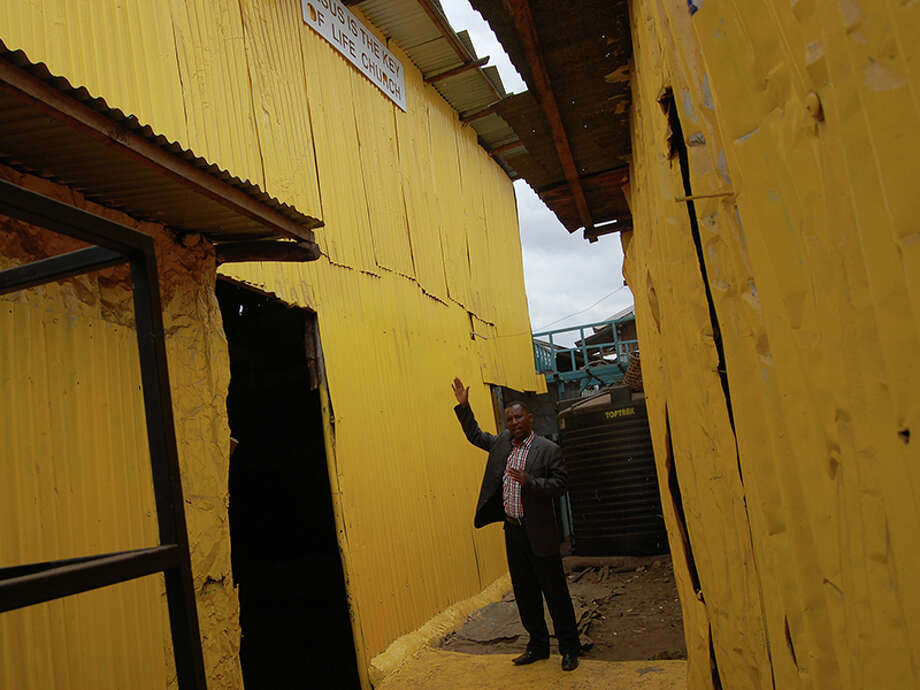 Pastor Steve Shirima, the leader of Jesus Is the Key of Life, shows off his yellow-painted Pentecostal church, which is located deep in the slums of Nairobi. Photo: Fredrick Nzwili/Religion News Se