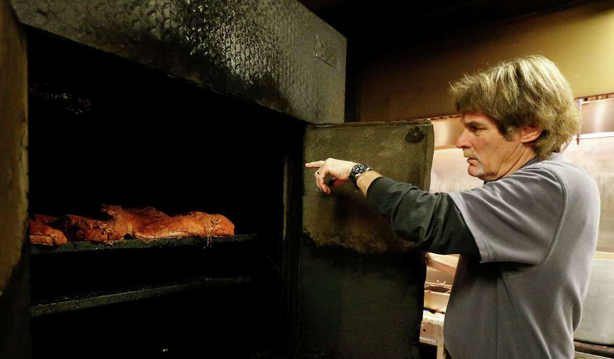 Lenox Bar-B-Q owner Erik Mrok points out beef brisket on one of his barbecue pits