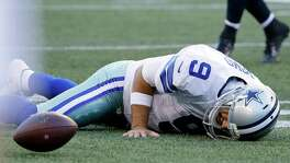 Dallas Cowboys quarterback Tony Romo lies on the turf after he went down on a play against the Seahawks during the first half of a preseason game on Aug. 25, 2016, in Seattle.