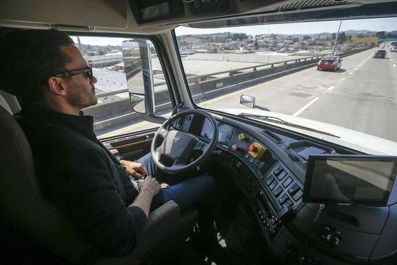 Matt Grigsby, senior program engineer at Otto, takes his hands off the steering wheel of the self-driving, big-rig truck during a demonstration on the highway, Thursday, Aug. 18, 2016, in San Francisco. Uber announced that it is acquiring self-driving startup Otto, which has developed technology allowing big rigs to drive themselves. (AP Photo/Tony Avelar)