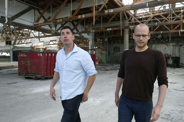 Danny Haber (left) and his business partner Yaniv Lushinsky discuss construction plans inside an abandoned warehouse at 1919 Market Street in Oakland, Calif. on Aug. 26, 2016, where their real estate development start-up firm Negev is building 63 live/work apartment units.