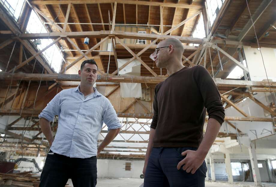 Danny Haber (left) and his business partner Yaniv Lushinsky discuss construction plans inside an abandoned warehouse at 1919 Market Street in Oakland, Calif. on Aug. 26, 2016, where their real estate development start-up firm Negev is building 63 live/work apartment units. Photo: Paul Chinn, The Chronicle