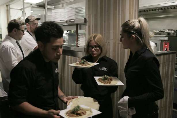 At a recent pop-up dinner at Restaurant Six Thirteen in Stamford hosted by chef Dini Klein, waiters and waitresses move food to the tables hot out of the kitchen as general manager Dan Weiss, back left, supervises.
