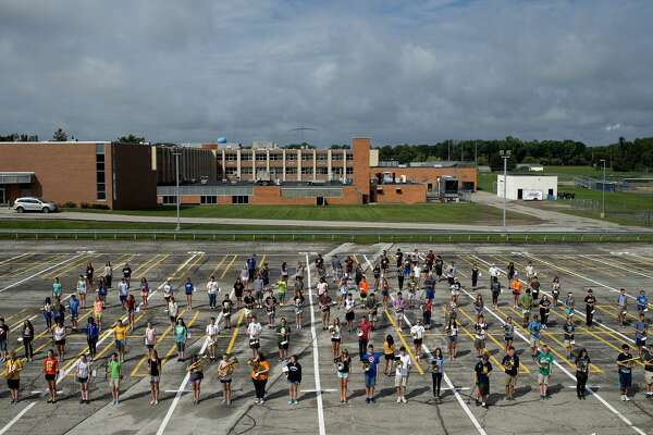 The Midland High marching band practice different formations on the school's practice field Thursday afternoon.