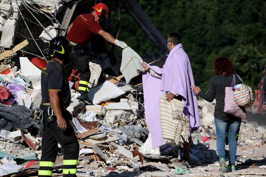 A man is given personal belongings after rescuers recovered the body of a woman from the collapsed house, in Amatrice, Friday, Aug. 26, 2016. Rescue crews have raced against time since a devastating earthquake leveled three towns in central Italy last Wednesday Aug. 23, leaving hundreds dead. (AP Photo/Andrew Medichini) ORG XMIT: AJM109 Photo: Andrew Medichini / Copyright 2016 The Associated Press. All rights reserved. This m